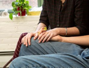 couple holding hands on a couch